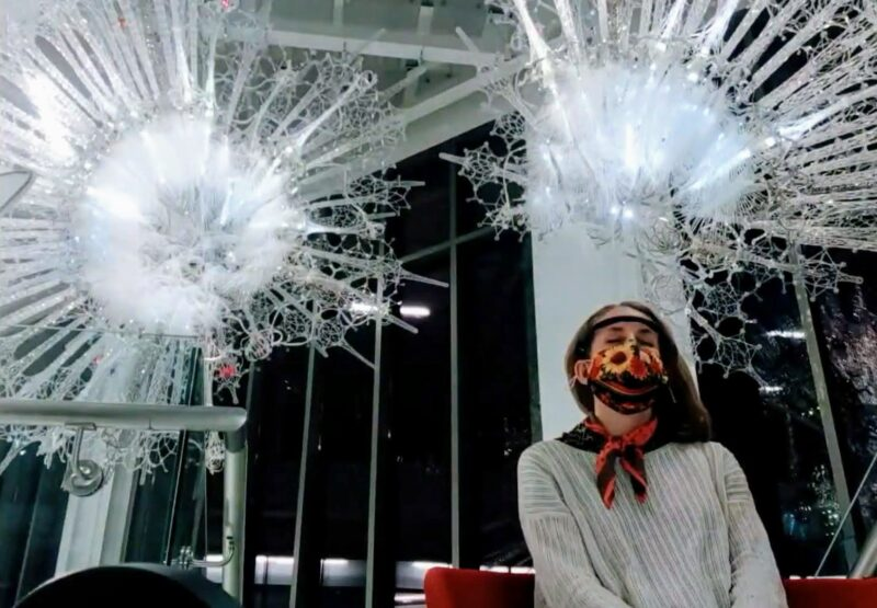 A woman sits beneath the Amatria sculpture wearing a Muse EEG Headset